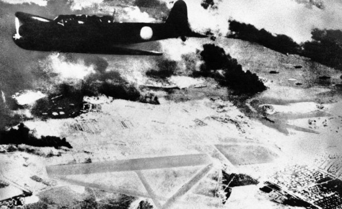 a-japanese-bomber-on-a-run-over-pearl-harbor-hawaii-is-shown-during-the-surprise-attack-of-dec-7-1941-black-smoke-rises-from-american-ships-in-the-harbor