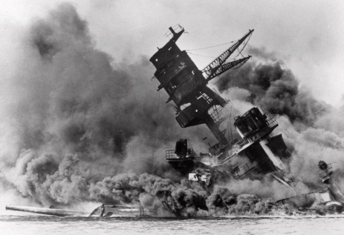 the-battleship-uss-arizona-belches-smoke-as-it-topples-over-into-the-sea