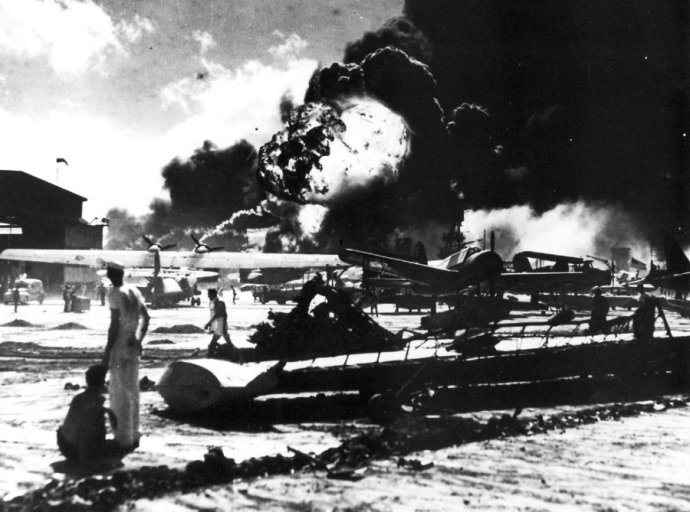 view-of-the-airfield-at-naval-air-station-ford-island-and-flames-from-burning-ships-in-the-background-taken-during-the-japanese-attack