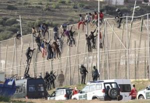 GRA089. MELILLA, 15/10/2014.- En torno a un centenar de inmigrantes permanecen encaramados en la valla fronteriza entre Melilla y Marruecos y se niegan a bajar como les indica la Guardia Civil, que mantiene un despliegue de seguridad en la zona de Villa Pilar, entre el aeropuerto de Melilla y el cementerio musulmán de Sidi Guariach.Numerosas patrullas de la Guardia Civil han formado un cordón de vehículos a pie de valla en un tramo amplio del perímetro, donde los subsaharianos permanecen desde pasadas las 06:30 horas, cuando se registró un intento de entrada masivo protagonizado por más de 200 inmigrantes.EFE/F. G. Guerrero